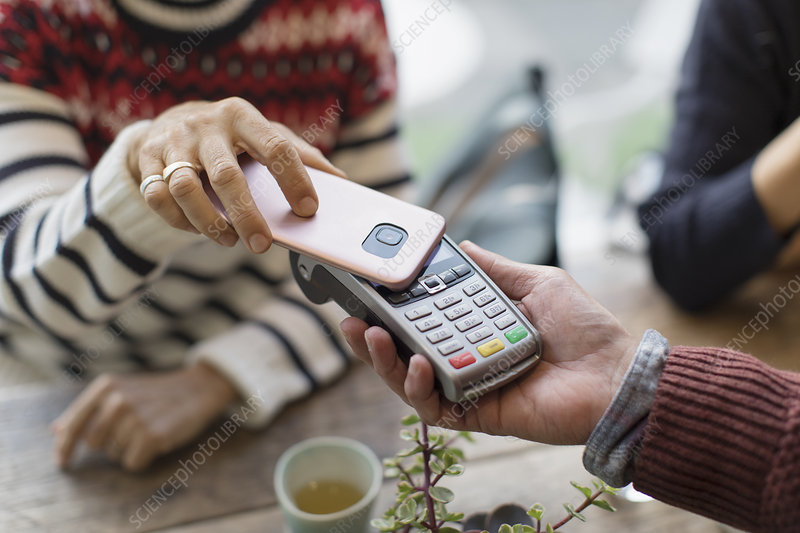 Woman with smart phone using contactless payment