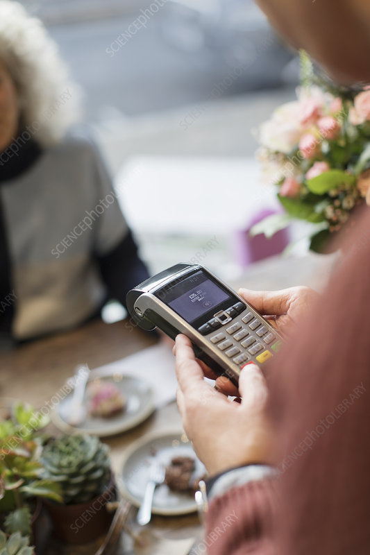 Cashier with credit card reader in cafe
