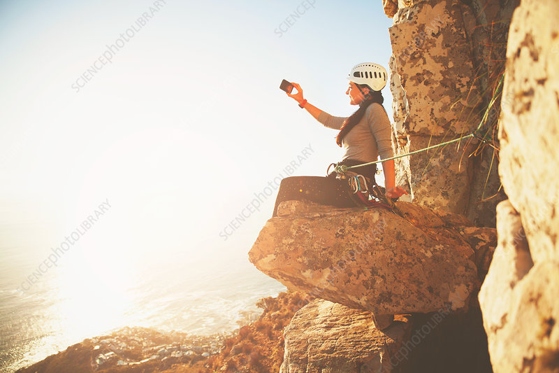 Female rock climber photographing sunny ocean view