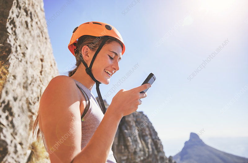 Smiling female rock climber using smart phone