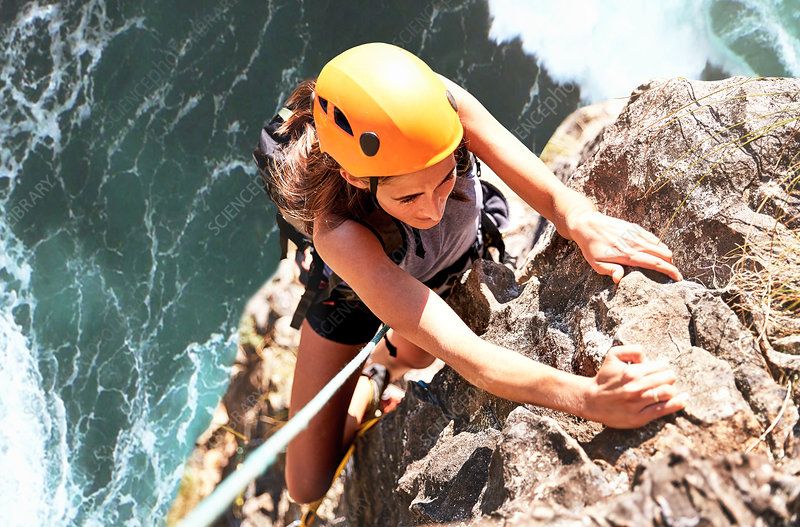 Focused rock climber hanging from rock above ocean