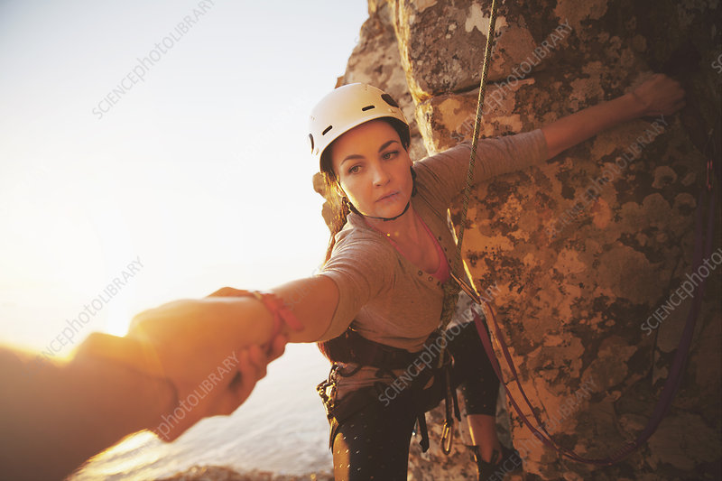 Focused female rock climber reaching for arm