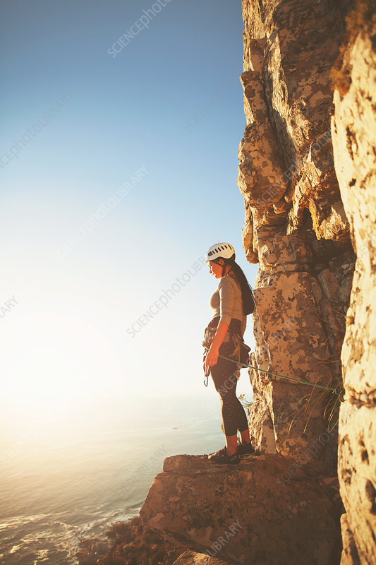 Female rock climber looking at sunny ocean view