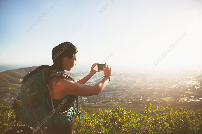 Female backpacker photographing sunny city view