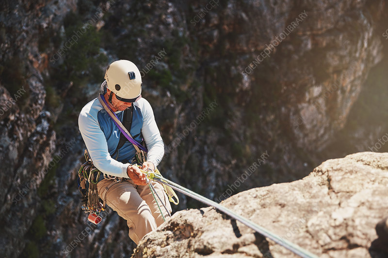 Male rock climber rappelling, descending from rope