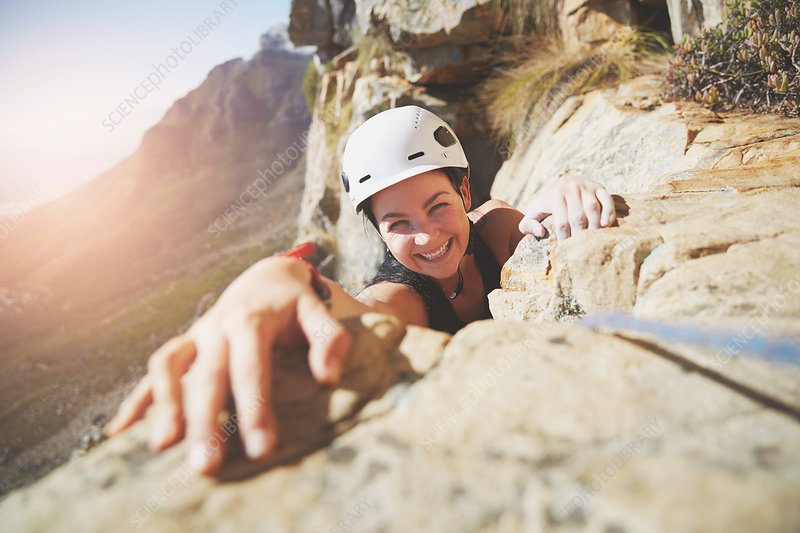 Portrait smiling, rock climber reaching for rock