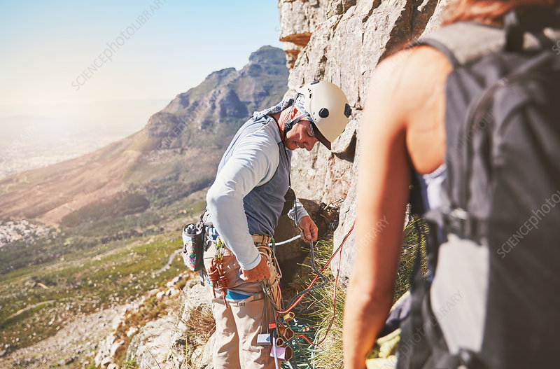 Male rock climber checking equipment