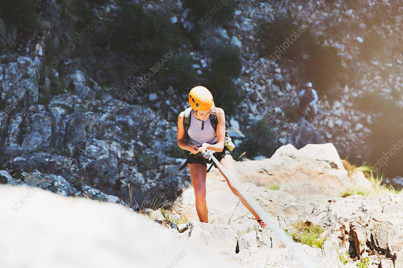 Female rock climber rappelling rock