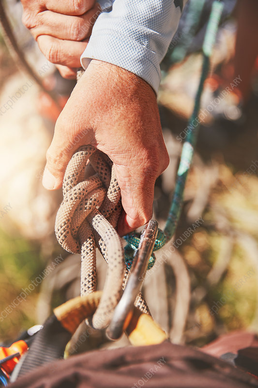 Close up rock climber holding knotted rope