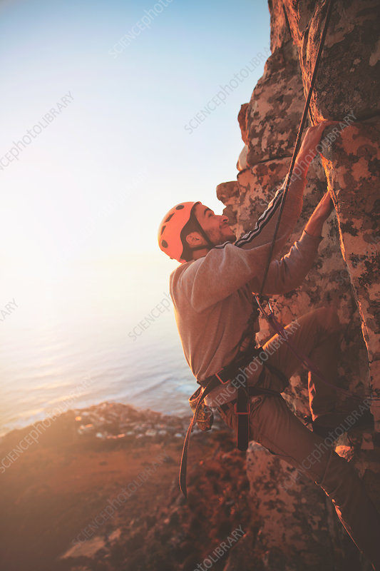 Male rock climber scaling rock