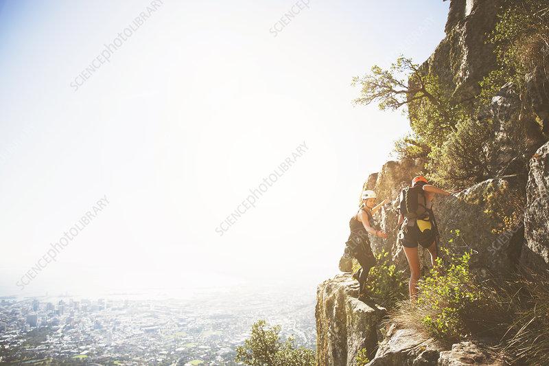 Rock climbers on sunny rocks above ocean