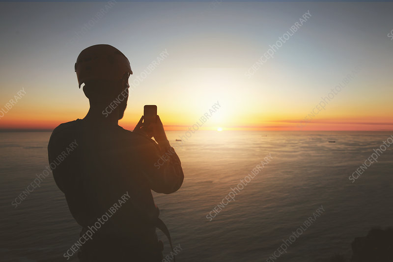 Silhouette rock climber photographing sunset