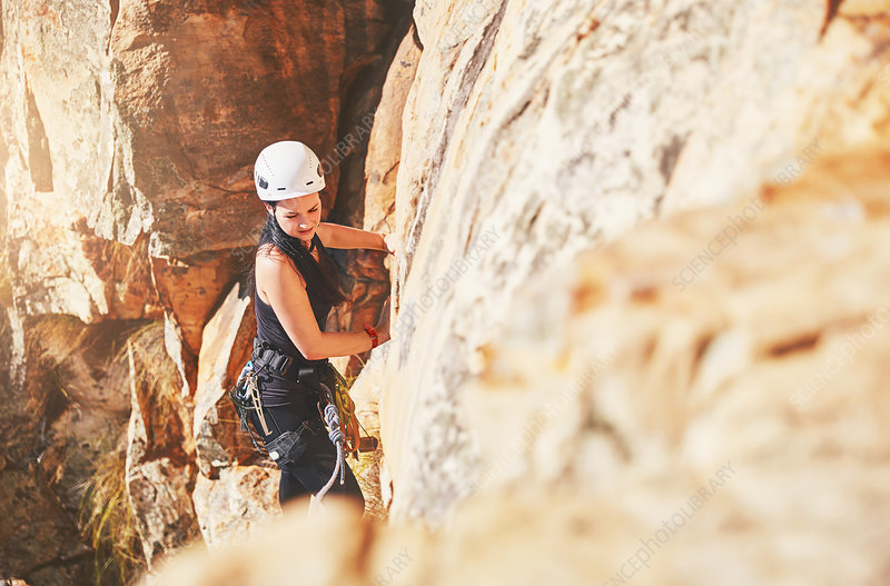 Female rock climber climbing rock