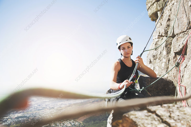 Portrait confident female rock climber with ropes