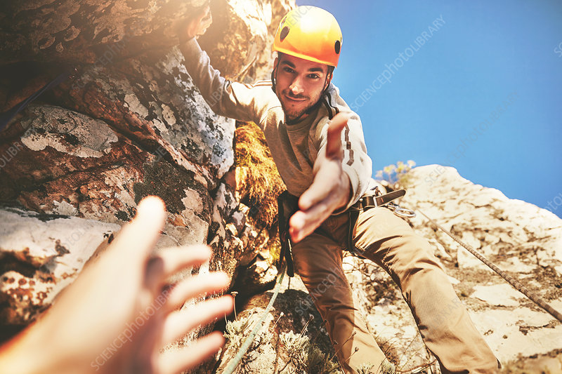 Reaching for hand of rock climber