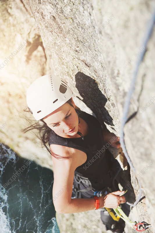 Determined, focused rock climber scaling rock