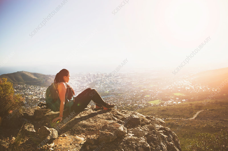 Serene backpacker sitting on rocks