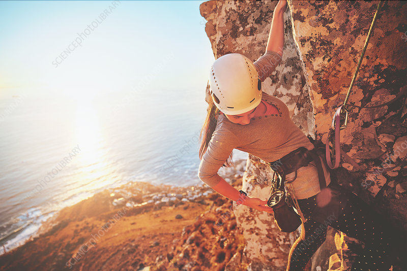 Female rock climber reaching for clip