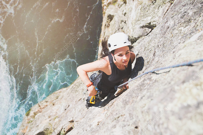 Focused, determined rock climber scaling rock