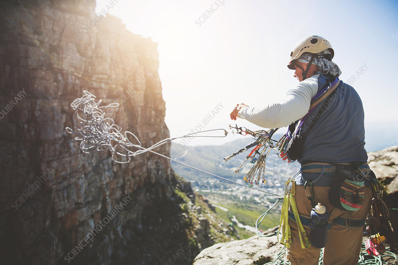 Male rock climber throwing rope
