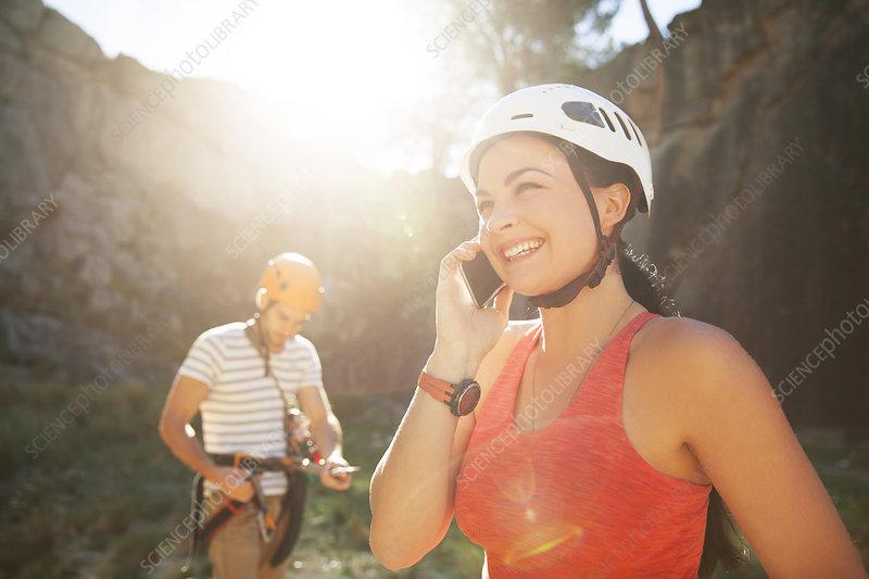 Smiling female rock climber talking on smart phone