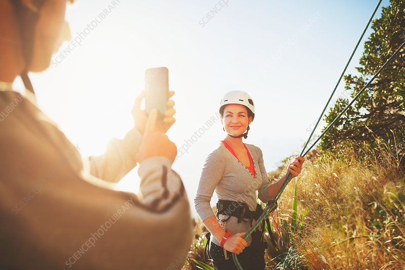 Female rock climber posing, being photographed
