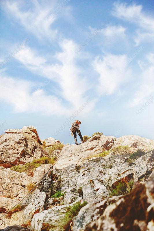Rock climber reaching top of rocks