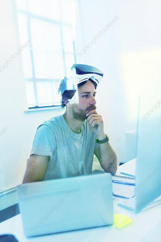 Focused computer programmer programming VR glasses