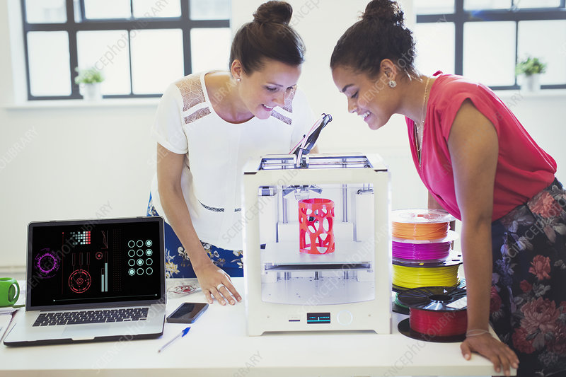 Female designers watching 3D printer in office