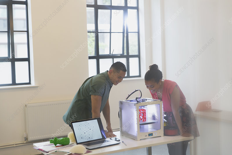 Designers watching 3D printer in office