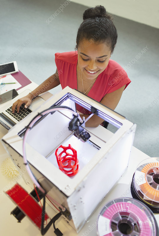 Smiling female designer watching 3D printer