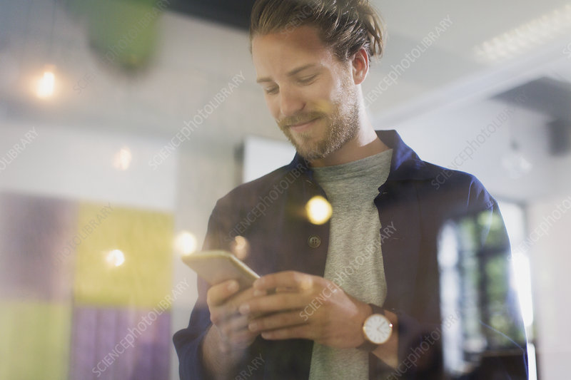 Smiling businessman texting with smart phone