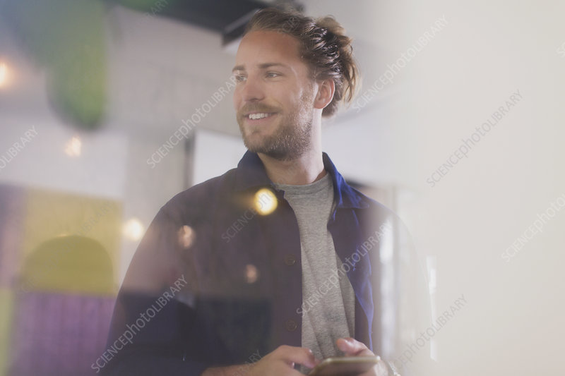 Smiling man texting with smart phone