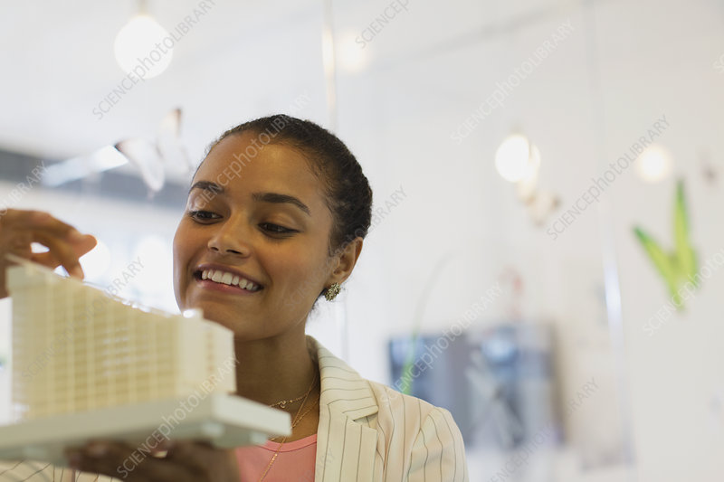 Smiling architect examining model