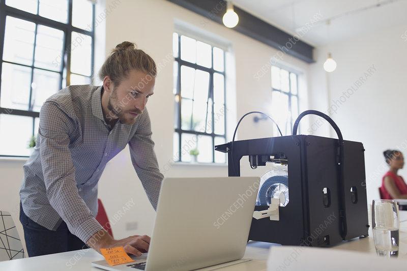 Male designer working at laptop next to 3D printer