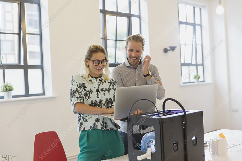 Designers using laptop at 3D printer in office