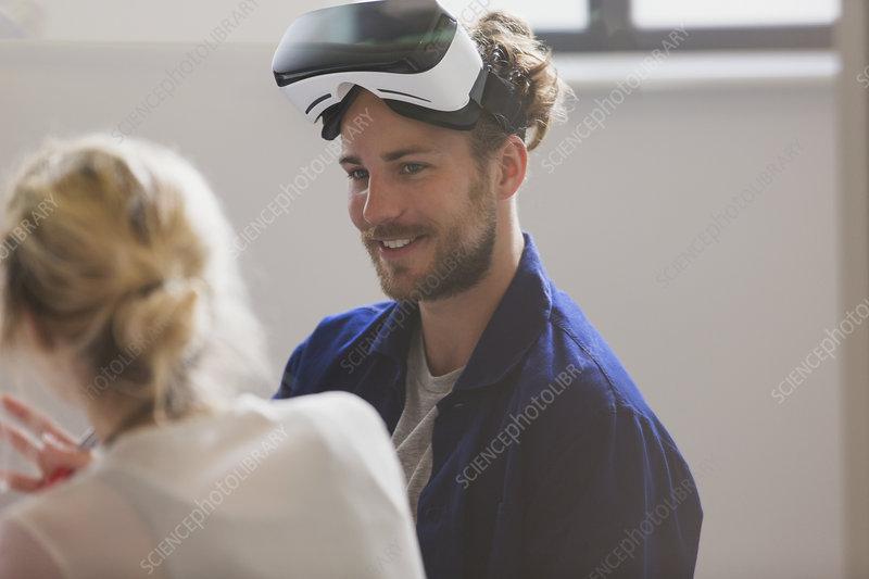 Smiling computer programmer wearing VR glasses