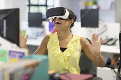 Enthusiastic businesswoman using VR glasses