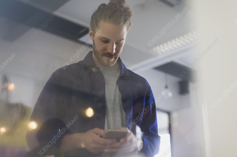 Businessman texting with smart phone in office