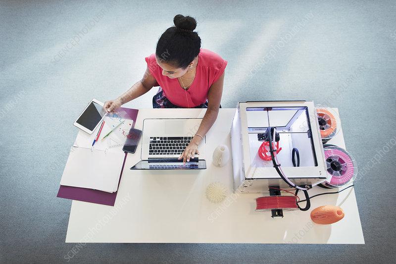 Female designer at laptop next to 3D printer