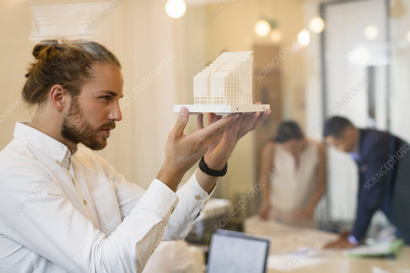 Focused, curious male architect examining model