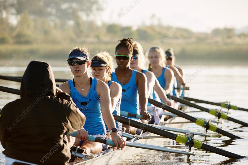 Female rowing team rowing scull on lake