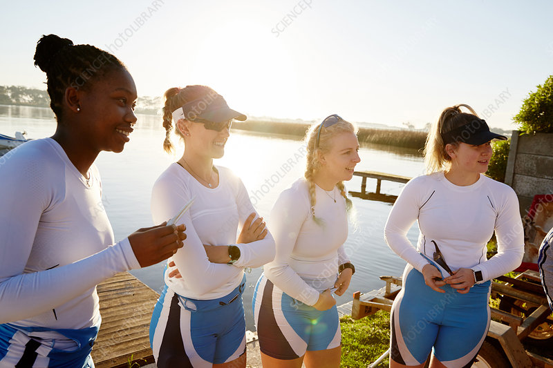 Female rowing team standing at sunny lakeside