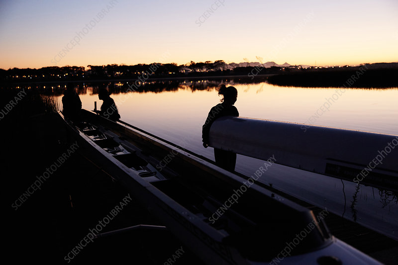 Female rowing team carrying scull at sunrise lake