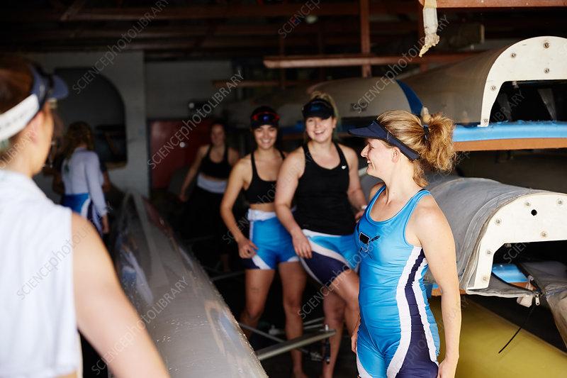 Female rowing team preparing in boathouse