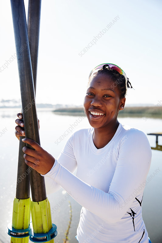 Portrait smiling rower holding oars