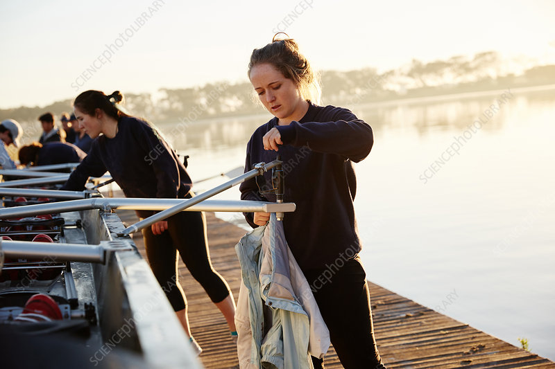 Female rowers preparing scullside dock