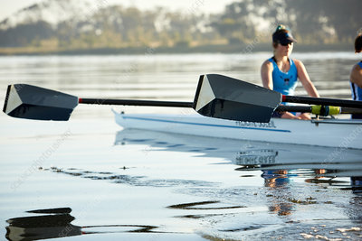 Female rower with oar rowing scull on lake