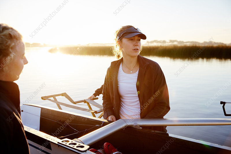 Focused rower lifting scull at sunrise lakeside