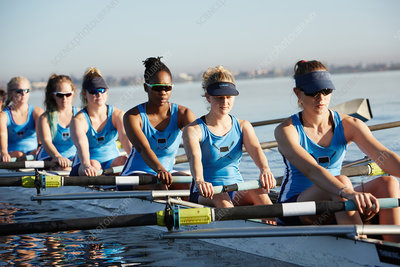 Female rowers rowing scull on sunny lake